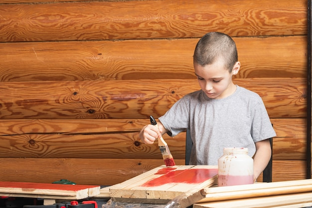 A boy paints a wooden fake with a paintbrush in red in a country house