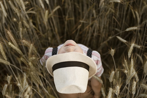 Boy in a panama hat looking up standing in a wheat field