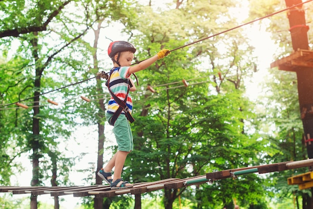 Boy passing the cable route high among trees. extreme sport in adventure park.