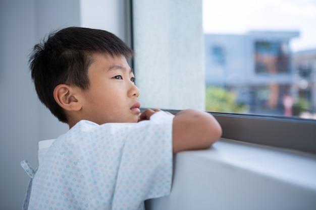 病院の窓から外を見て少年患者