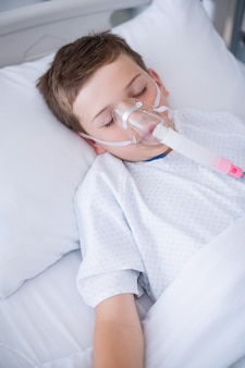 Boy patient wearing oxygen mask lying on hospital bed