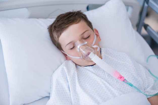 病院のベッドに横になっている酸素マスクを身に着けている男の子の患者