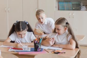 Boy peeping into notebooks of girls