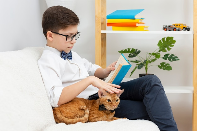 Boy petting cat and reading