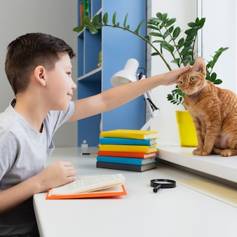 Boy petting cat while reading