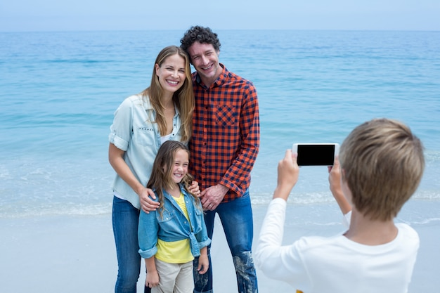 Boy photographing happy family at sea shore