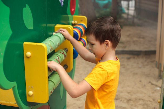 A boy at the playground plays a game, rear view. children's sports, leisure, hobbies.