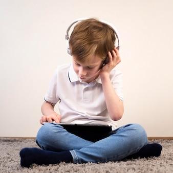 Мальчик играет в видеоигру на своем планшете