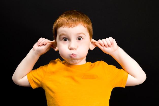 Мальчик играет и держится за уши