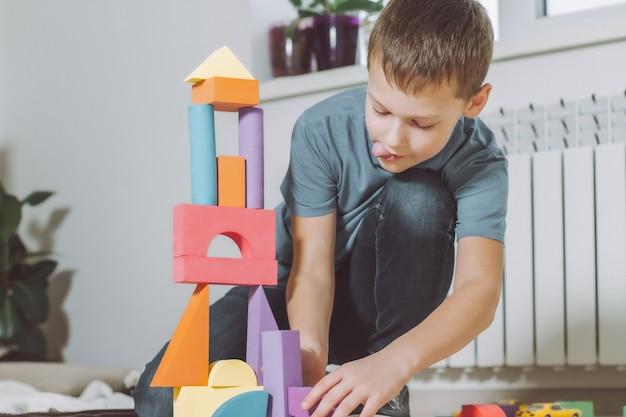 Мальчик играет дома на полу с конструктором геометрических фигур