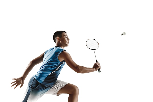 Boy playing badminton isolated on white wall.