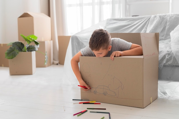 Boy playing in a box before moving out with his family