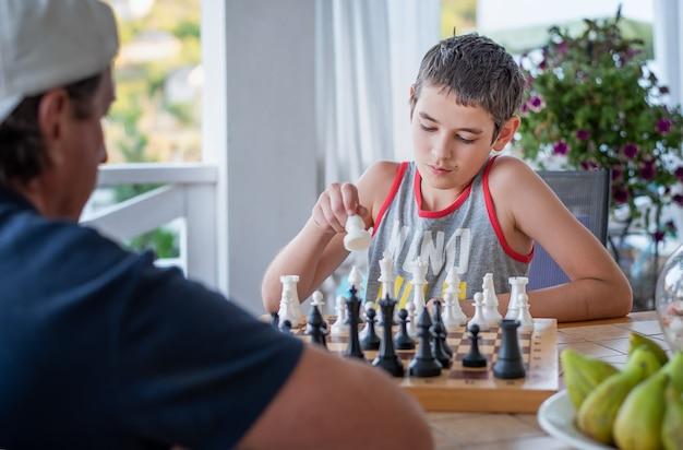 男とチェスをしている少年