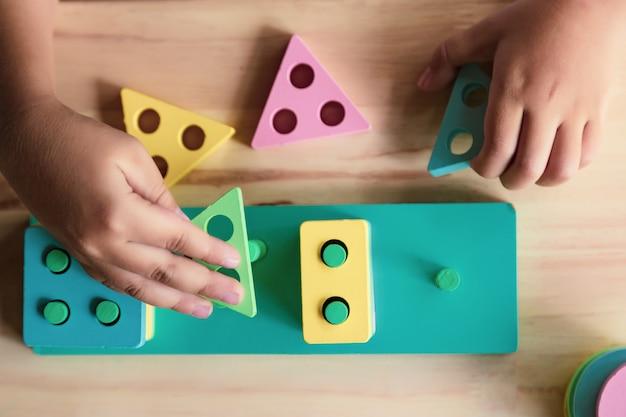スキルを学ぶために子供のおもちゃを遊んでいる少年