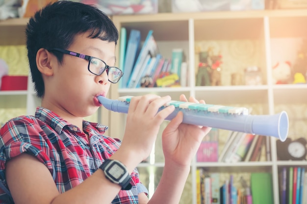 Boy playing the clarinet, trumpet at home, blowing a sweet flute, musicology background