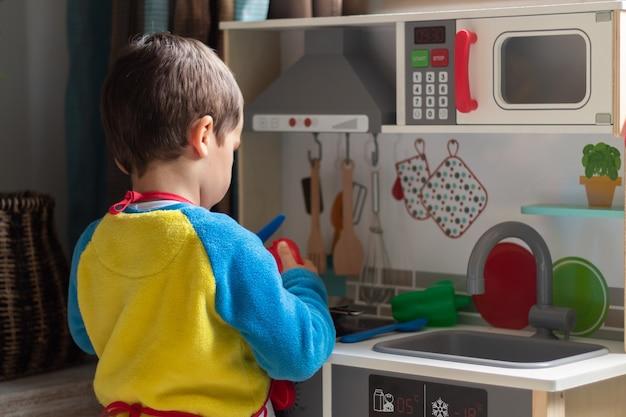 Мальчик играет повара с игрушечной кухней дома