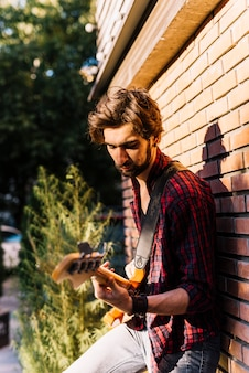 Boy playing the electric guitar standing on brick wall