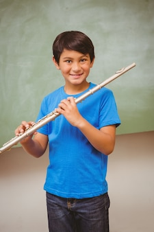 Boy playing flute in classroom