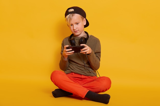 Boy playing game via cell phone, adorable male kid sitting isolated on yellow and holding mobile, guy dresses casually, posing with headphones around neck, keeping legs crossed.