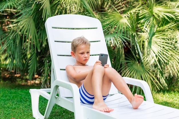 전화로 게임을 하는 소년. 해변 컨셉에서 휴가를 보내는 동안 아이들을 위한 가제트 의존성 장애 문제