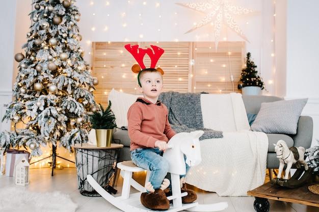 Мальчик играет возле елки с новым годом и рождеством христовым украшенный интерьер