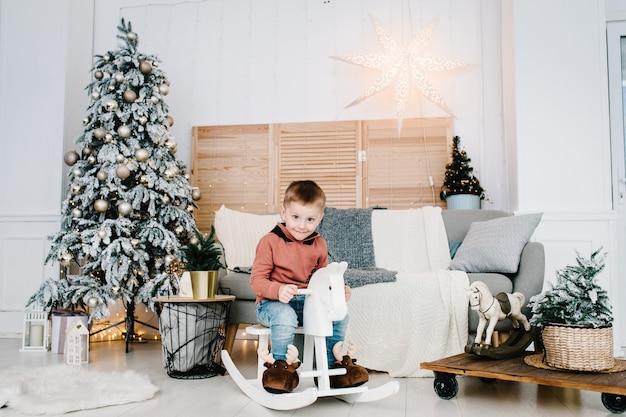 Мальчик играет возле елки с новым годом рождество оформленный интерьер