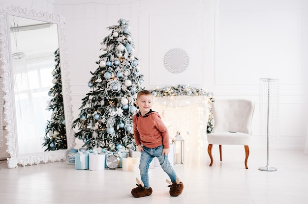 Boy playing near christmas tree.  merry christmas. christmas decorated interior. the concept of family holiday.