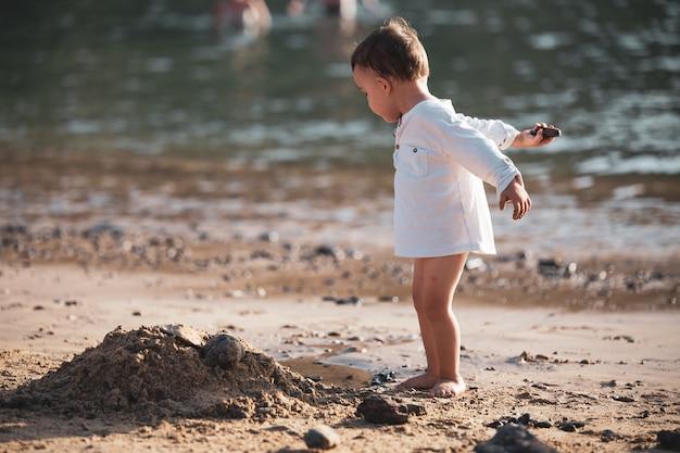 石でビーチで遊ぶ少年