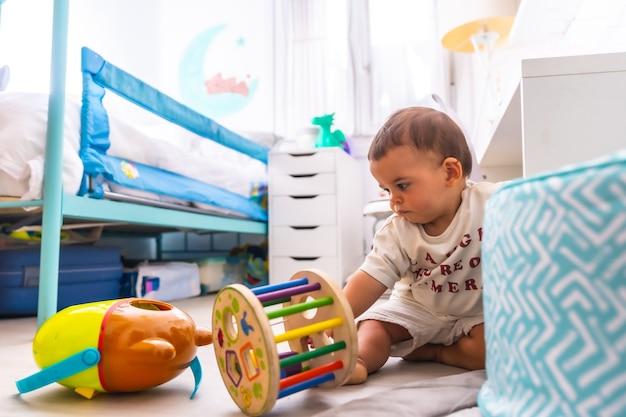 床がおもちゃで遊んでいる少年