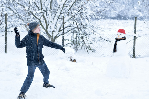 Мальчик играет в снежки рядом со снеговиком, веселые зимние развлечения