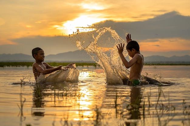 日没時に川でスプラッシュ水を再生する少年、スプラッシュ水、タイ
