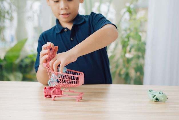 Boy playing toy cars on table