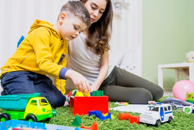 Boy playing toys with woman