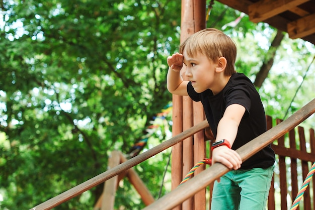 Boy playing in a tree house and looking into the distance. kid enjoying time in adventure park on summer day. summer activities for kids. child having fun on school vacations. adventure park for kids.