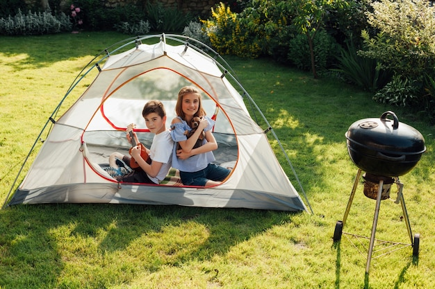 Boy playing ukulele sitting back to back his sister in tent near barbecue grill