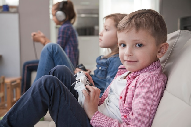 Boy playing video game with sister