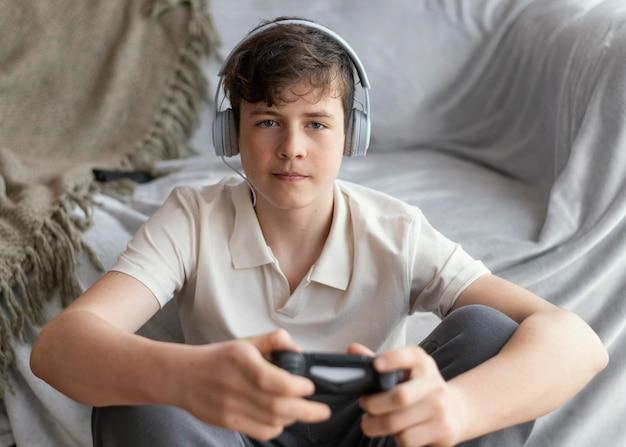 Ragazzo che gioca videogioco a casa
