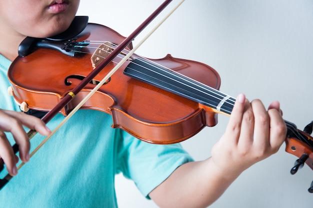 少年が部屋でバイオリンを弾く