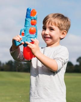 Мальчик играет с водным пистолетом, вид спереди