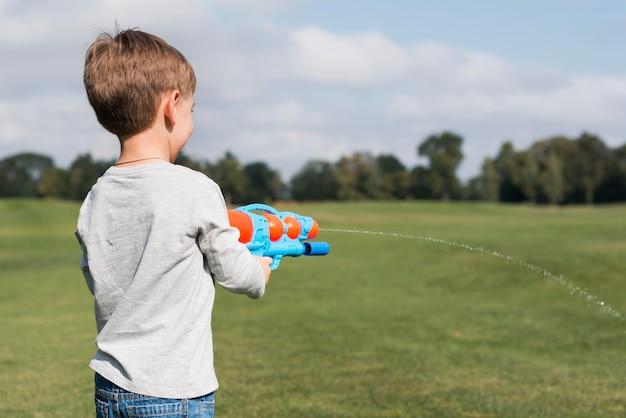 Мальчик играет с водяным пистолетом через плечо