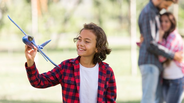 Boy playing with airplane and defocused parents at the park
