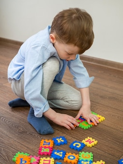 Boy playing with alphabet game at home
