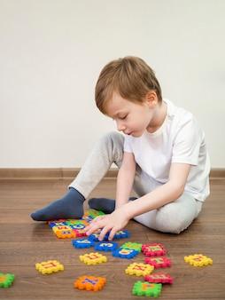 Мальчик играет с алфавитом в помещении