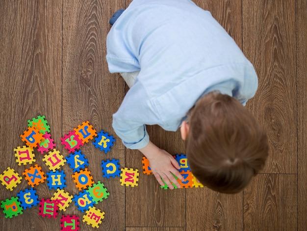 Мальчик играет с алфавитом