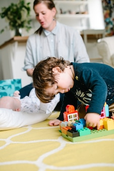 Boy playing with building blocks at home on the floor