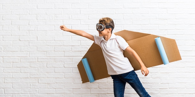 Boy playing with cardboard airplane wings flying
