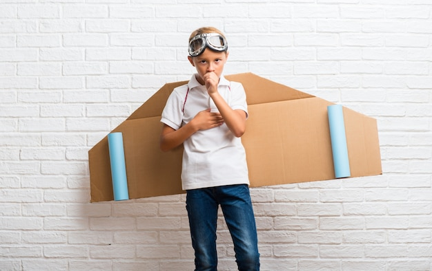 Boy playing with cardboard airplane wings on his back is suffering with cough and feeling bad