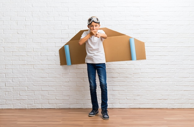 Boy playing with cardboard airplane wings on his back pointing with finger at someone