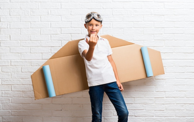 Boy playing with cardboard airplane wings on his back presenting and inviting to come