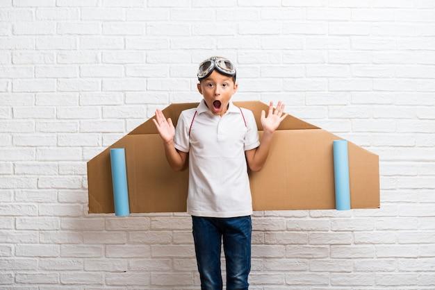 驚きとショックを受けた表情で彼の背中に段ボールの飛行機の翼で遊んでいる少年